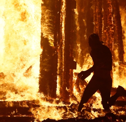 """Burning Man participant runs into the flames of the """"Man Burn"""" at the Burning Man arts and music festival in the Black Rock Desert of Nevada"""